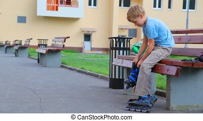 boy sits on bench in foreyard and puts on roller skates