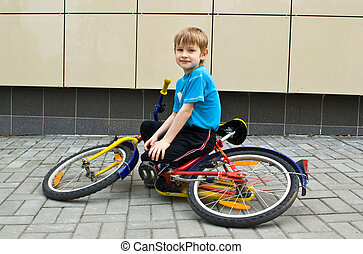 Boy sits on bicycle