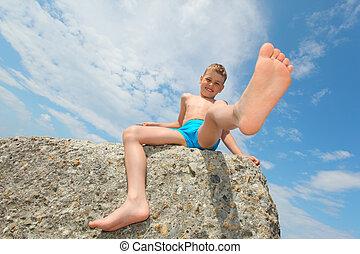 boy sits on rock, bottom view