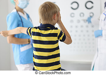 Boy sits with his back at ophthalmologist's appointment, ...