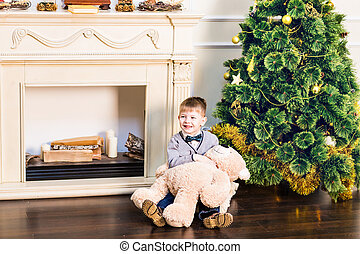 Boy sits with teddy bear in the background of the Christmas tree.