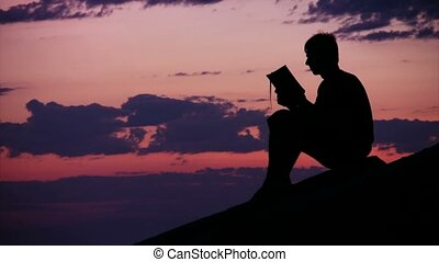 boy sitting against sunset sky and reads book