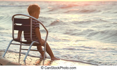 Boy sitting alone on the chair by sea