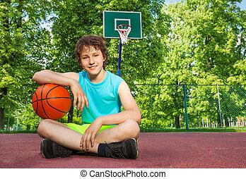 Boy sitting alone with elbow on the ball - Boy sitting on...