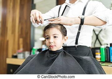 Boy Sitting At Hairdresser Salon For Haircut