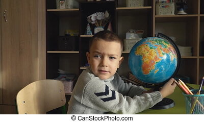 boy sitting at his desk with a globe