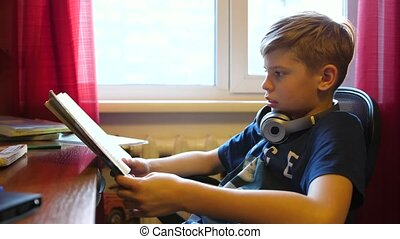 Boy sitting at school Desk and does the job. School education. Reading of books.