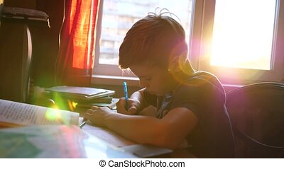 Boy sitting at school Desk and does the job. School education. The sun's rays through the glass.