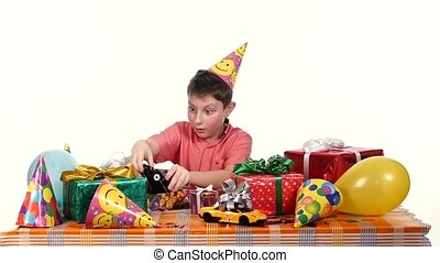 Boy sitting at the table and considers all their gifts, choosing what he likes. slow motion