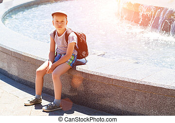 boy sitting by the fountain on a Sunny day