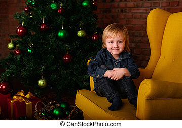 boy sitting in a chair near the Christmas tree