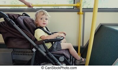 Boy sitting in baby stroller in bus - Side view of adorable...