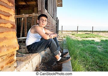 Boy sitting in barn