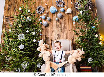 Boy sitting in chair near Christmas tree