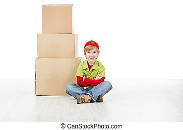 Boy sitting in front of carton boxes pyramid