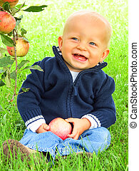 Boy sitting in grass holding apple