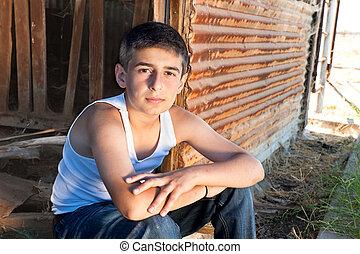 Boy sitting in old barn