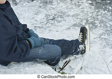 boy sitting in snow with ice skates