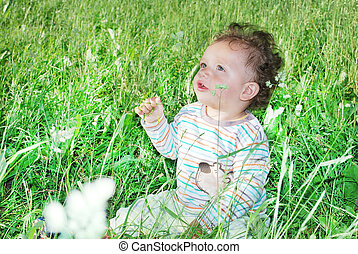 boy sitting in tall grass - In the summer, the boy sitting...