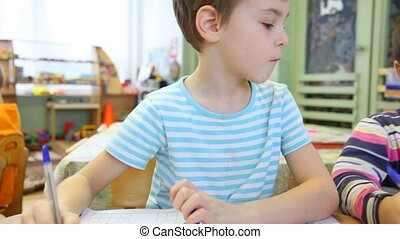 Boy sitting in the classroom and watching to the left