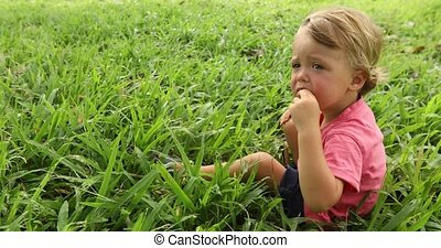 Boy sitting in the grass outside