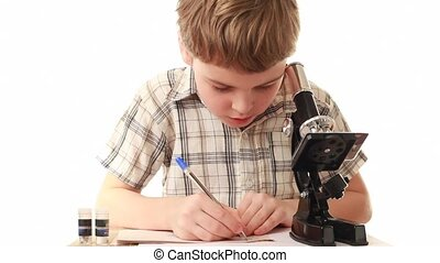 Boy sitting near microscope writes something in notebook