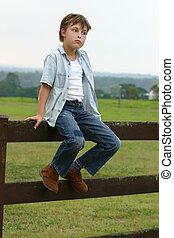 Boy sitting on a fence - Farm boy sitting on a wooden fence...