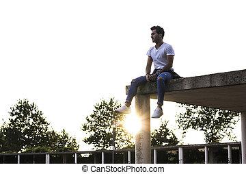 boy sitting on a ledge