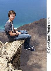 boy sitting on a rock