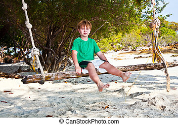 boy sitting on a swing at the beach under trees