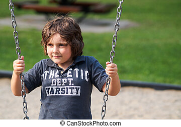 Boy sitting on a swing
