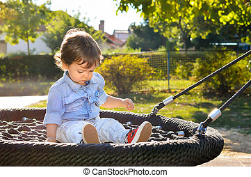 Boy sitting on a swing in the park