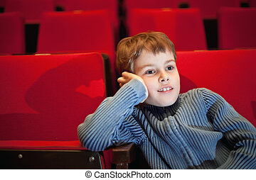 boy sitting on armchairs at cinema, steadfastly looking