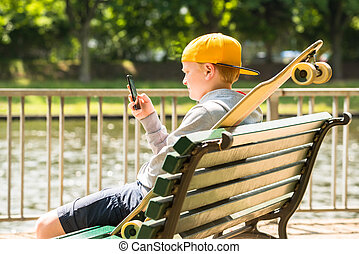 Boy Sitting On Bench Using Mobile Phone