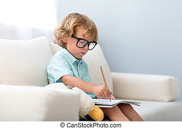 Boy sitting on couch and drawing
