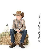 boy sitting on hay bale