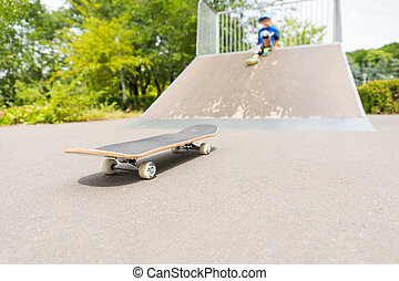 Boy Sitting on Ramp Looking Down at Skateboard