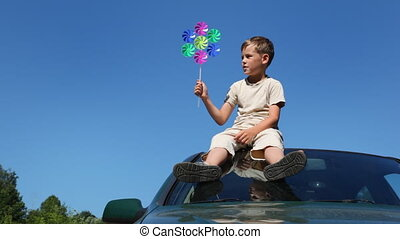 boy sitting on roof of car against blue sky summer day, holding in his hand toy from seven small colored decks, which rotate wind