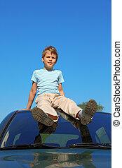 boy sitting on roof of car, blue sky