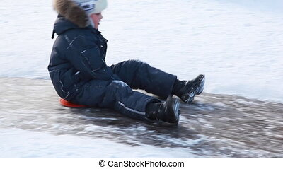 Boy sitting on sled moves down for ice slide - boy sitting...