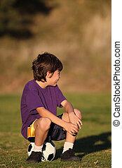 Boy sitting on soccer ball