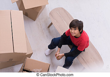 boy sitting on the table with cardboard boxes around him top view