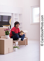 boy sitting on the table with cardboard boxes around him