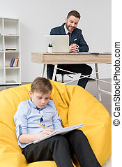 Boy sitting on yellow pillow and drawing while his father businessman working at office