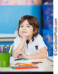Boy Sitting With Hand On Chin In Drawing Class