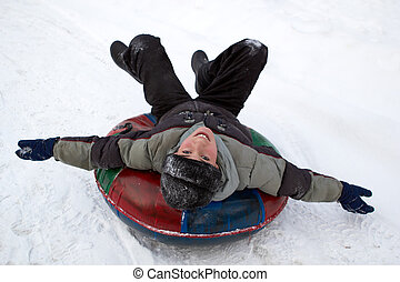 boy sledding down a snowy hill on a color inflatable sled