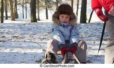 Boy sledding on snow. Active fun for family Christmas vacation