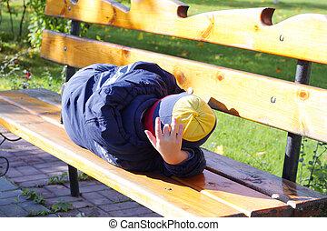 Boy sleeping on bench