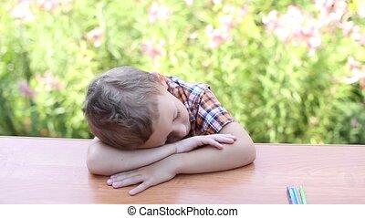 Boy sleeping on desk - A tired, weary or bored student at...