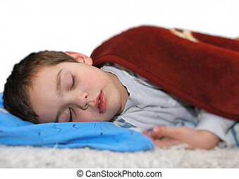 Boy sleeping - a boy is sleeping on a bed covered with a...